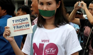 An activist against the junta-backed constitution seals her mouth with duct tape. Seven activists were jailed on Friday.