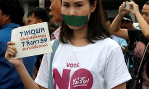 And activist against the junta-backed constitution seals her mouth with duct tape and holds a placard ahead of this month's referendum in Thailand.