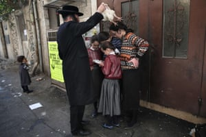 An ultra-Orthodox Jewish man swings a chicken over his family as they perform the Kapparot ceremony in the Jerusalem neighbourhood of Mea Shearim