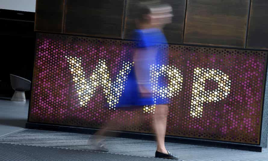 woman walks past WPP sign