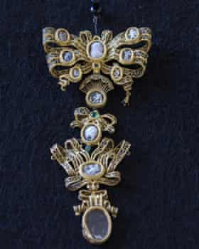 A gold brooch against a dark blue background