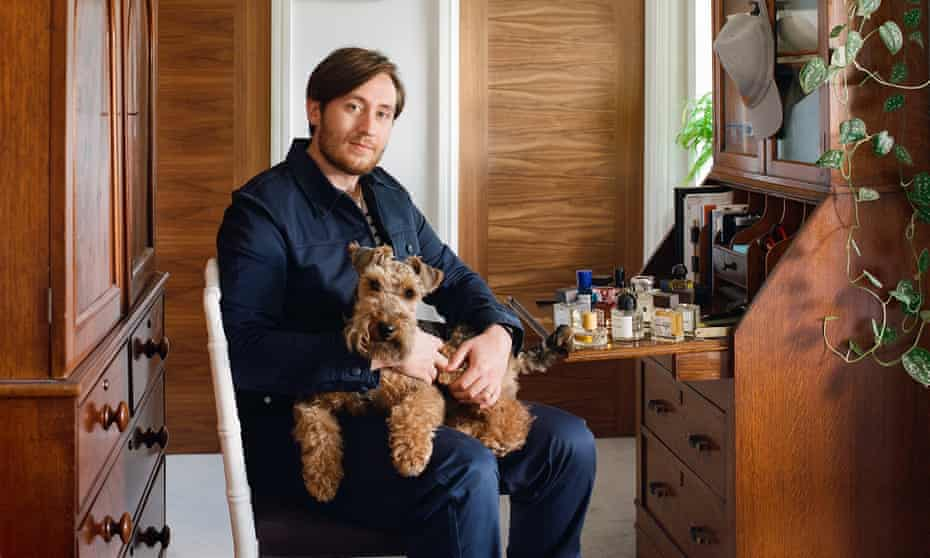 Nick Carvell with his dog on his lap and his collection of perfumes on an opened antique desk surface