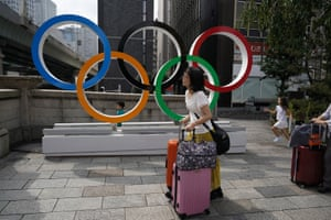 Tourists walk with their luggage past the Olympic rings in Tokyo.