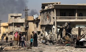 Civilians stand outside their homes in west Mosul, 9 March, caught up in battles between Iraqi forces and Isis.