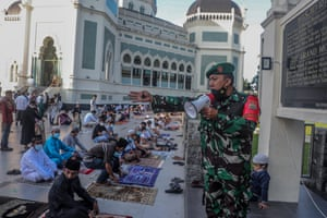 A military man gives directions for physical distancing before Eid Al-Adha prayers amid the Covid-19 pandemic at Al-Mashun Grand Mosque, in Medan, North Sumatra, Indonesia.