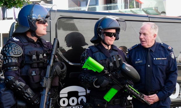 Victorian police assistant commissioner Chris O'Neill (right) and two public order response officers show new non-lethal weapons the police force say are required to combat violent protests.