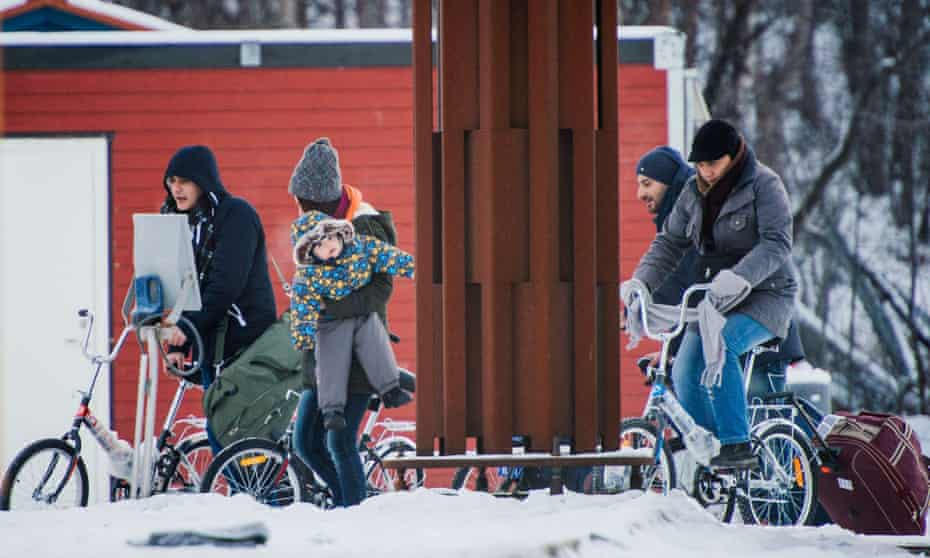 Refugees walk to the Norwegian border crossing station at Storskog