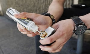 A vaper refills his electronic cigarette with vaping liquid.