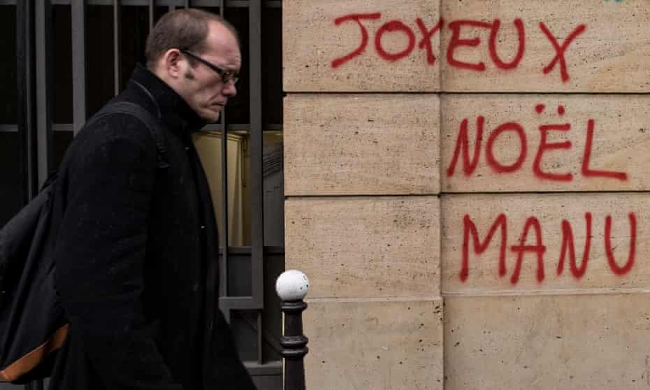 Graffiti on a wall near the Champs Élysées reads 'Merry Christmas, Manu' as anger at Emmanuel Macron's government spilled over into a fourth weekend of violent protests.