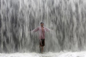 Mumbai, India A boy stands under an overflowing dam along the Powai lake after heavy rains