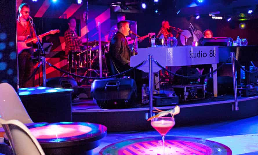 A band playing on a stage with a cocktail on a table in the foreground and a neon wash over the whole scene
