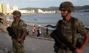 'Welcome to Acapulco': soldiers stand guard near the resort's main tourist beach.