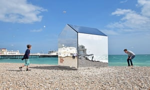 Passersby admire a beach hut made from mirrors, designed by ECE Architecture, on Worthing beach, West Sussex. The mirrors enable the hut to merge into its surroundings.