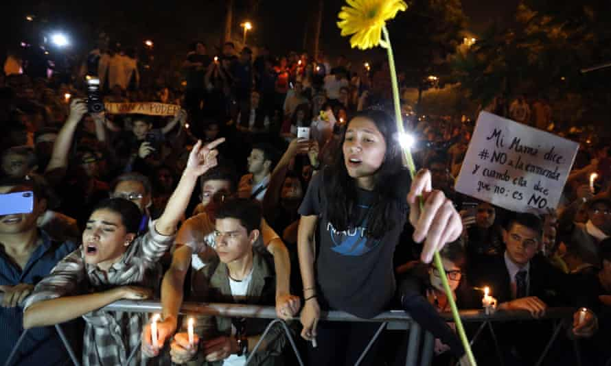 Youths offer flowers to the police during a gathering to reject the constitutional amendment in Asuncion, Paraguay.