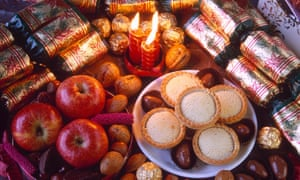 Table with Christmas food and candles.