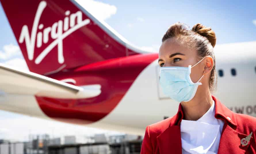 Masked cabin crew by a Virgin plane