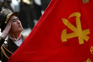 A soldier salutes at a flag adorned with the hammer, sickle and paintbrush