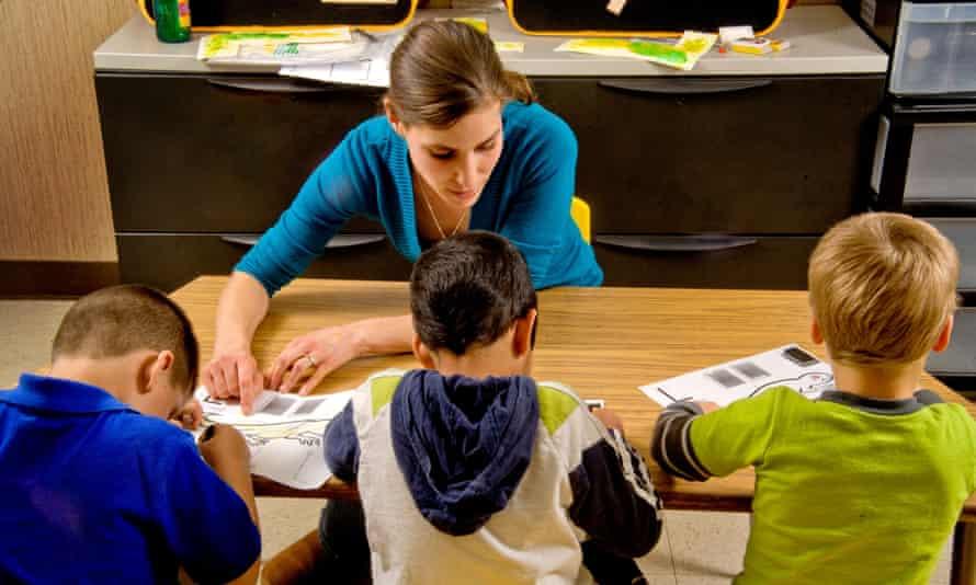 A teacher helps boys to colour.
