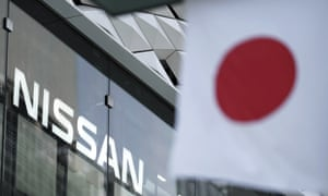Nissan logo is seen near a Japanese flag at the automaker's showroom
