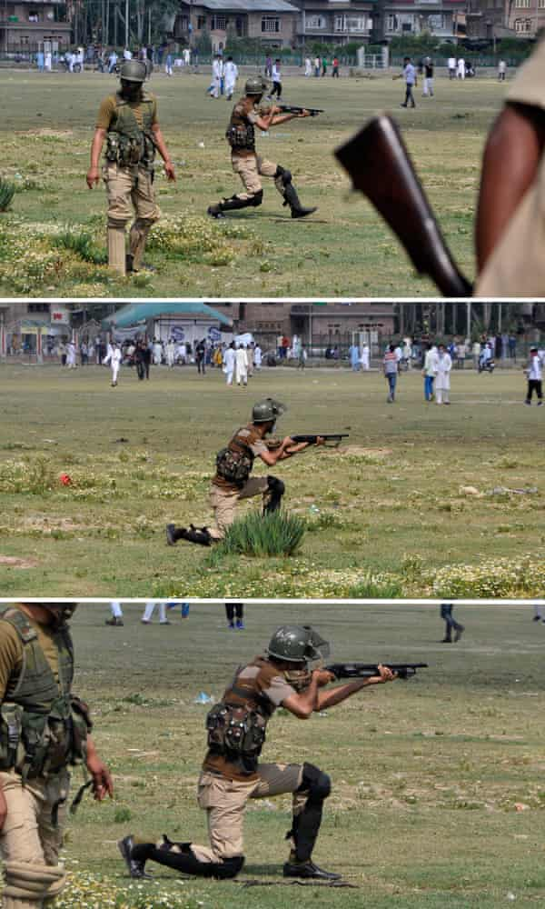 An Indian policeman aims a pellet gun towards Kashmiri protesters in Srinagar in July.
