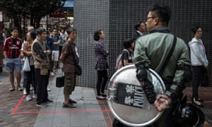Police watch as people queue in front of a polling station in Hong Kong
