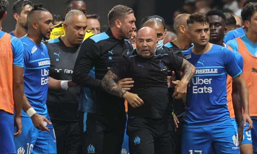 Marseille manager Jorge Sampaoli is led away from the chaos.