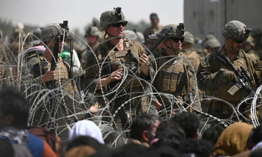 US soldiers stand guard behind barbed wire as Afghans sit on a roadside near the military part of the airport in Kabul