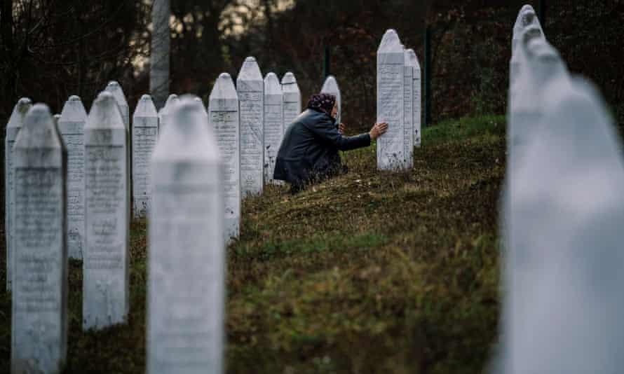 A Bosnian woman prays near a grave of her relative at the memorial centre of Potocari near Srebrenica
