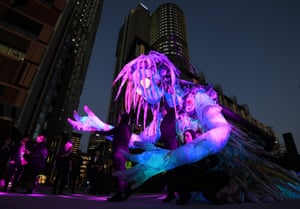 A team of performers move a six-metre creature illuminated with lights at Barangaroo during Vivid Sydney