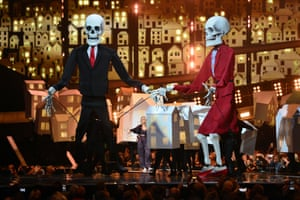Hand in hand, puppets depicting Donald Trum and Theresa May on stage as Katy Perry performs at the Brits