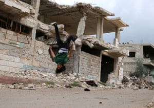 Parkour coach Ibrahim al-Kadiri, 19, demonstrates his Parkour skills near damaged buildings in the rebel-held city of Inkhil, west of Deraa, Syria, April 7, 2017. The team records their performances in photos and videos, which they post on social media.