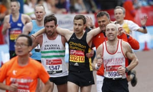 A runner is helped near the finish line during the 2017 London marathon