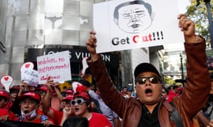 Pro-democracy demonstrators hold pictures of Thai prime minister and junta leader Prayuth Chan-ocha on Sunday after elections look set to be delayed again.