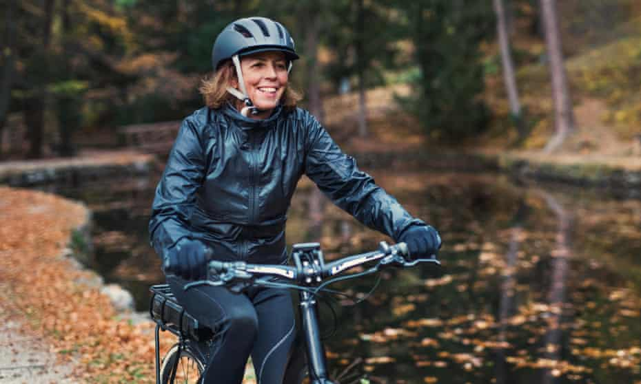 A senior woman with e-bike cycling outdoors on a road in park in autumn
