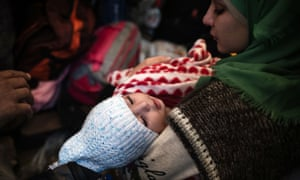 A woman holds a child as refugees take shelter in the village of Berkasovo
