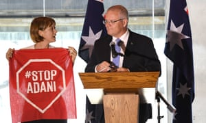 A Stop Adani protester takes to the stage where Scott Morrison was making a speech in Brisbane on Monday