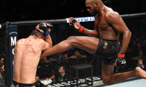 Jon Jones kicks Dominick Reyes during their light heavyweight championship bout