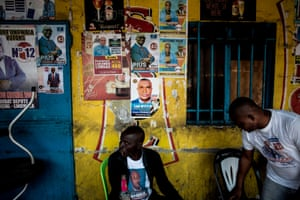 Men sit in front of a bar covered with campaign posters in the Lingwala district