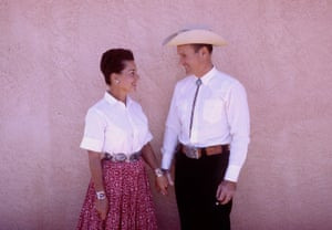 A Texan couple against a pink wall