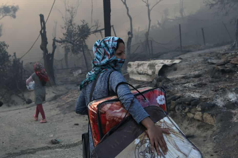 A migrant carries her belongings after being driven from Moria camp by the fire.