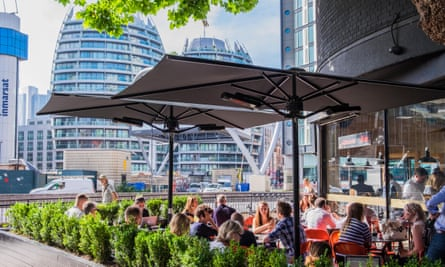 Young people sit in a bar with the high-rise offices of London's 'silicon roundabout' in the background