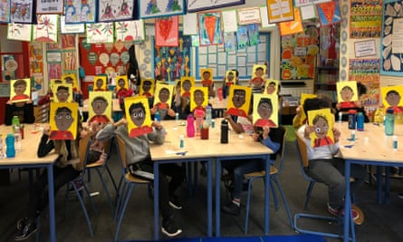 Children in a south London primary school hold up their portraits of Marcus Rashford.