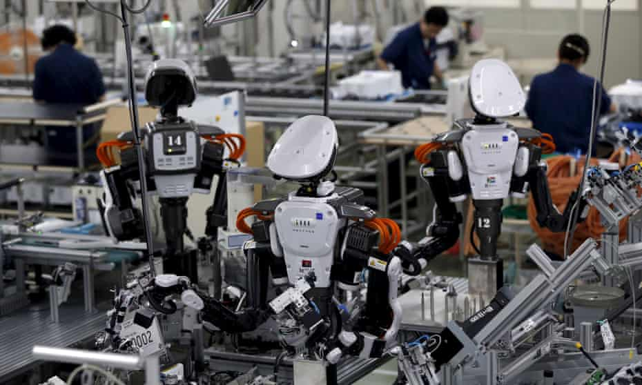 Humanoid robots work side by side with employees in the assembly line at a factory in Kazo, Japan.
