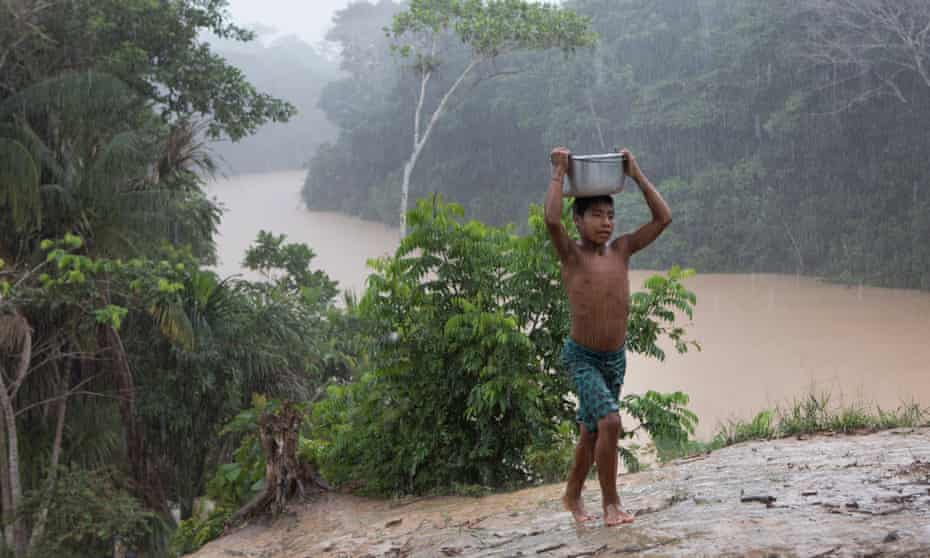 A young Marubo boy, Metsisi Marubo, carries water from the Rio Itui toward the village of Rio Novo