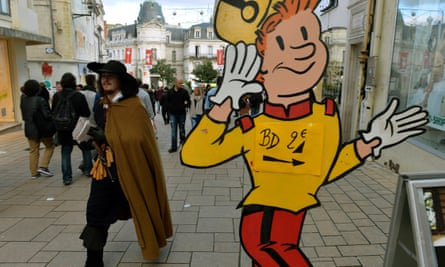 A man in a caped costume walks past a sign advertising comics for sale at the Angoulême festival this weekend.