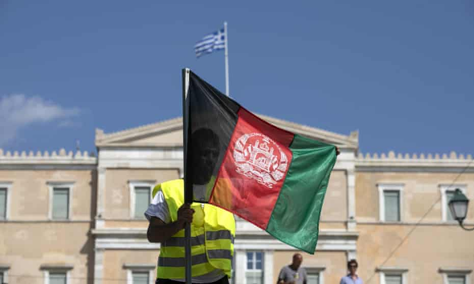 A person unfolds an Afghan flag in front of the parliament in Athens