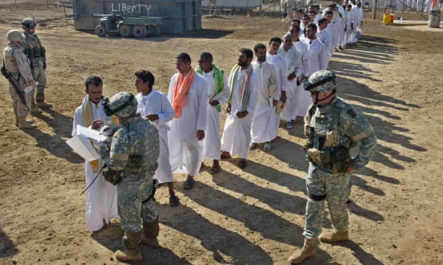 Detainees are checked by US soldiers during a prisoner release at Abu Ghraib prison on 1 October 2005.