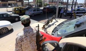一名利比亚部队成员在首都的黎波里以西萨布拉塔的一个检查站处理秘密移民问题