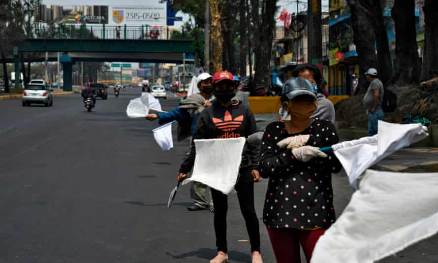 People wave white flags as a signal they need food, along a highway in Guatemala City.