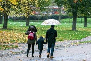 A family in Green Park on rainy and blustery day in London.
